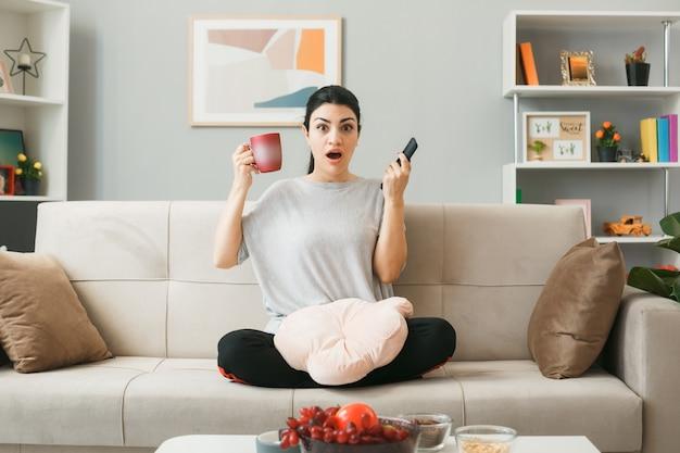 Jonge vrouw met kussen met tv-afstandsbediening met kopje thee zittend op de bank achter de salontafel in de woonkamer