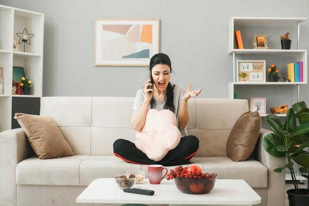 Jonge vrouw met kussen spreekt aan de telefoon zittend op de bank achter de salontafel in de woonkamer