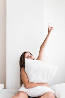 Jonge vrouw met kussen zittend op bed naar boven gericht