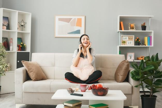 Jonge vrouw met kussen zittend op de bank achter de salontafel spreekt aan de telefoon in de woonkamer
