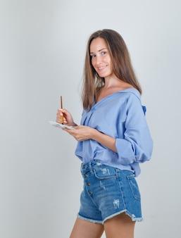Jonge vrouw met kwast over palet in shirt, korte broek en op zoek vrolijk.