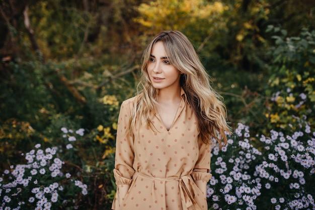 Jonge vrouw met lang blond golvend haar glimlachend staande naast een struik met paarse bloemen