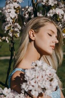 Jonge vrouw met lang blond haar buiten in een park genietend van zonnig weer