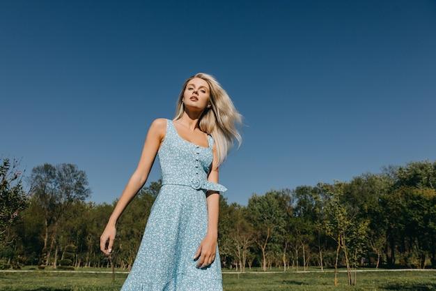 Jonge vrouw met lang blond haar, gekleed in een blauwe jurk die zich voordeed op een blauwe hemelachtergrond buitenshuis