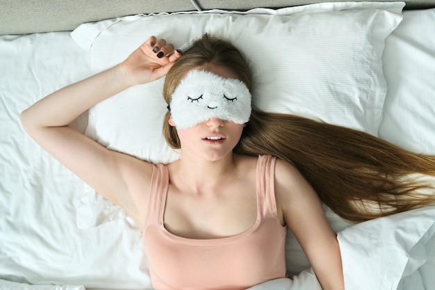 Jonge vrouw met lang blond haar met slaapmasker in haar ogen slapen in wit bed, bovenaanzicht