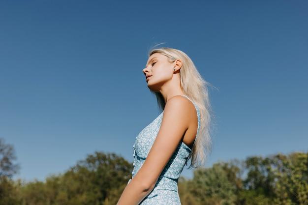 Jonge vrouw met lang blond haar op blauwe hemelachtergrond buitenshuis