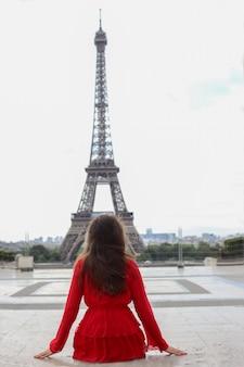 Jonge vrouw met lang bruin haar in rode jurk leunt achterover en kijkt naar de eiffeltoren