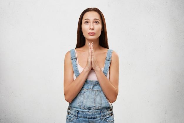 Jonge vrouw met lang donker steil haar opzoeken hopelijk bidden met haar handen gevouwen