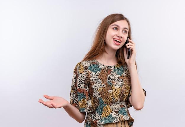Jonge vrouw met lang haar die kleurrijke kleding dragen die tijdens het spreken op mobiele telefoon over witte muur glimlacht