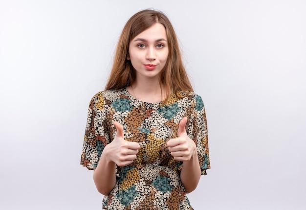 Jonge vrouw met lang haar die kleurrijke kleding dragen die zelfverzekerd duimen opdagen met beide handen die zich over witte muur bevinden