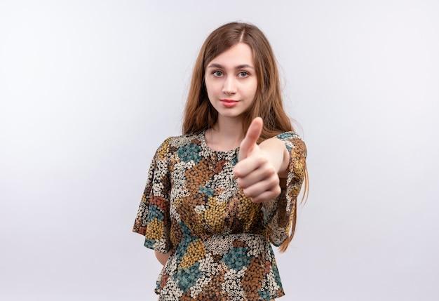 Jonge vrouw met lang haar die kleurrijke kleding dragen die zelfverzekerd duimen toont die zich over witte muur bevinden