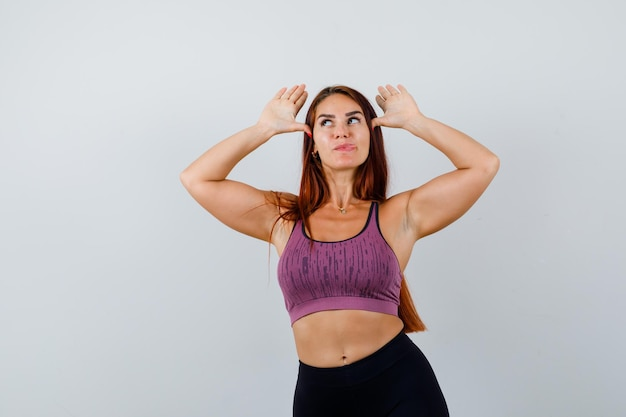 Jonge vrouw met lang haar die sportkleding draagt