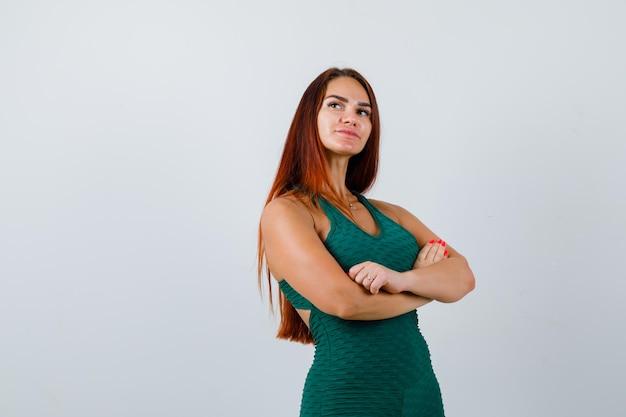 Jonge vrouw met lang haar, gekleed in een groene bodycon