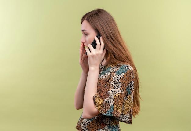 Jonge vrouw met lang haar, gekleed in kleurrijke jurk verrast en verbaasd praten over mobiele telefoon staande over groene muur