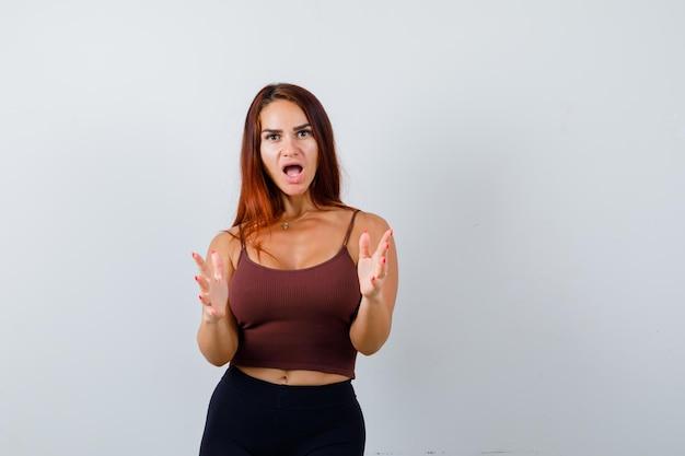 Jonge vrouw met lang haar in een bruine crop top