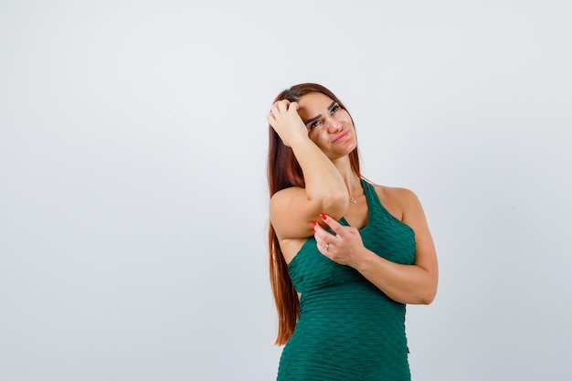 Jonge vrouw met lang haar in een groene bodycon