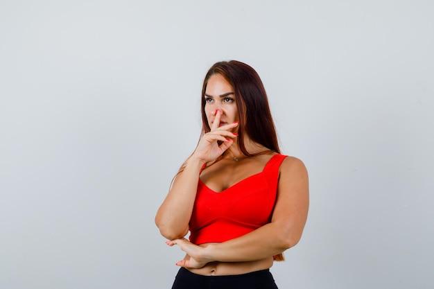 Jonge vrouw met lang haar in een oranje tanktop