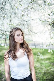 Jonge vrouw met lang haar in een witte t-shirt onder de bloeiende bomen