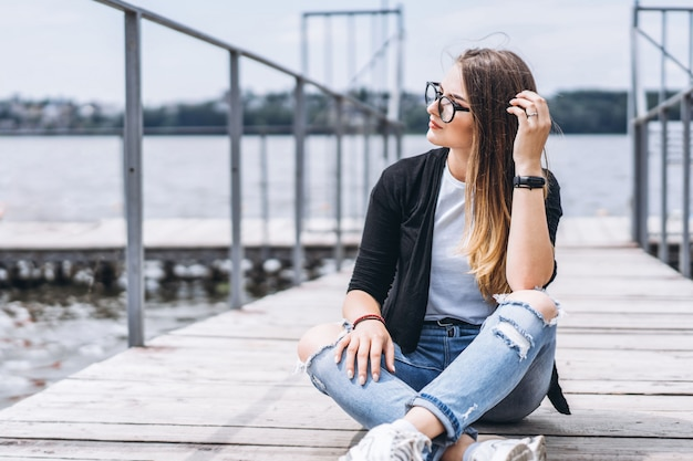 Jonge vrouw met lang haar in stijlvolle glazen die zich voordeed op een houten pier in de buurt van het meer. het meisje kleedde zich in jeans en t-shirt glimlachend en kijkend