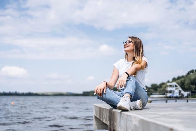 Jonge vrouw met lang haar in stijlvolle glazen poseren op de betonnen kust in de buurt van het meer. het meisje kleedde zich in jeans en t-shirt die weg glimlachen kijken