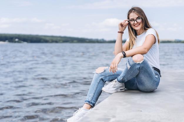 Jonge vrouw met lang haar in stijlvolle glazen poseren op de betonnen kust in de buurt van het meer. het meisje kleedde zich in jeans en t-shirt glimlachend en bekijkend de camera