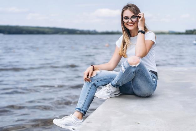 Jonge vrouw met lang haar in stijlvolle glazen poseren op de betonnen kust in de buurt van het meer. vrouw gekleed in jeans en t-shirt glimlachen en kijken