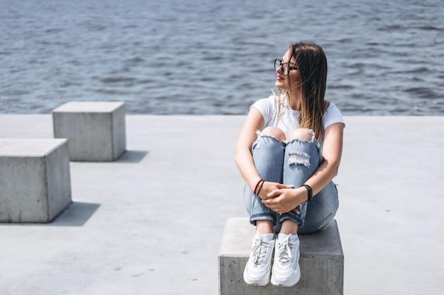 Jonge vrouw met lang haar in stijlvolle glazen poseren op de betonnen kust in de buurt van het meer. vrouw gekleed in jeans en t-shirt glimlachend en wegkijken