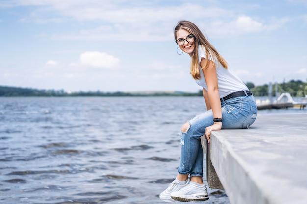 Jonge vrouw met lang haar in stijlvolle glazen poseren op de betonnen kust in de buurt van het meer