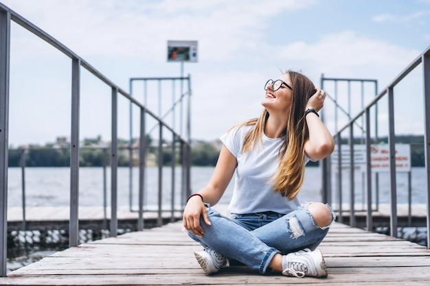 Jonge vrouw met lang haar in stijlvolle glazen poseren op een houten pier in de buurt van het meer. het meisje kleedde zich in jeans en t-shirt glimlachend en bekijkend de camera