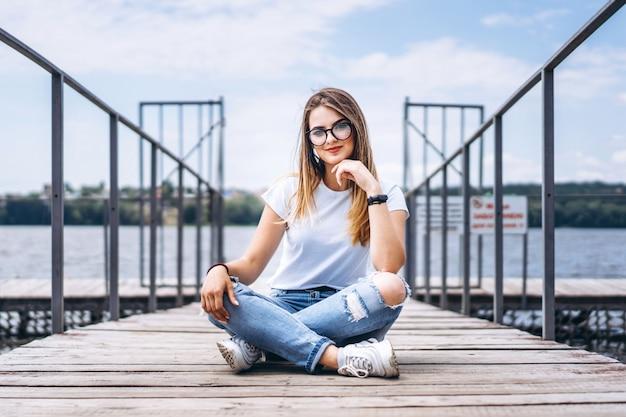 Jonge vrouw met lang haar in stijlvolle glazen poseren op een houten pier in de buurt van het meer. vrouw gekleed in jeans en t-shirt glimlachen en kijken