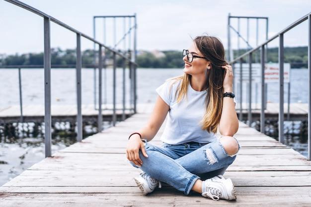 Jonge vrouw met lang haar in stijlvolle glazen poseren op een houten pier in de buurt van het meer