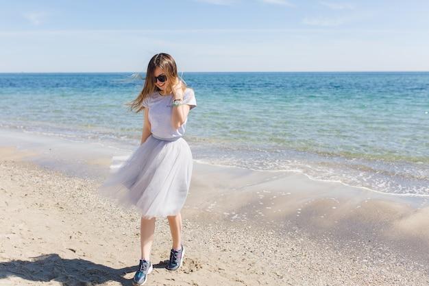 Jonge vrouw met lang haar loopt in de buurt van blauwe zee