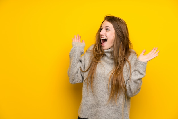 Jonge vrouw met lang haar op gele achtergrond met verrassing gelaatsuitdrukking