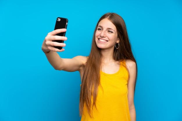 Jonge vrouw met lang haar over geïsoleerde blauwe muur die een selfie maakt