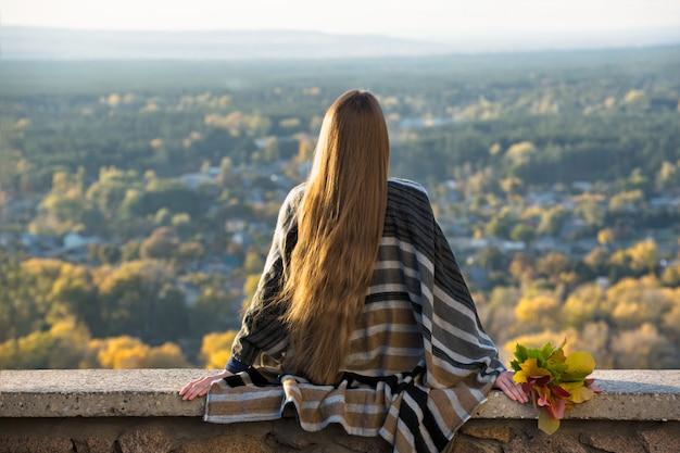 Jonge vrouw met lang haar zit op een heuvel met uitzicht op de stad. achteraanzicht