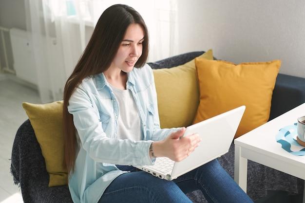 Jonge vrouw met lang haar zit thuis op de bank en werkt op laptop