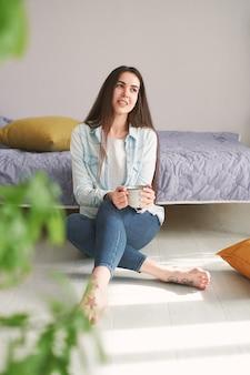 Jonge vrouw met lang haar zit thuis op de vloer en drinkt koffie
