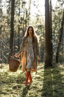 Jonge vrouw met lang rood haar in een linnenkleding die paddestoelen in het bos verzamelen