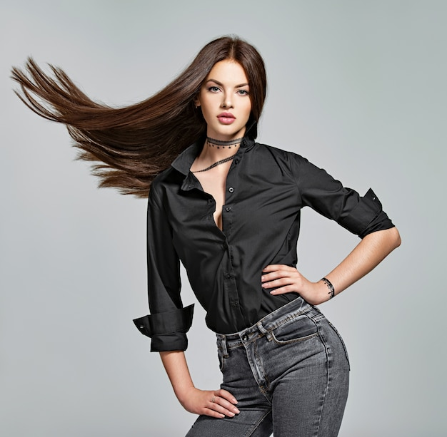Jonge vrouw met lang steil haar - in de studio. portret van een aantrekkelijk donkerbruin meisje. mannequin draagt een zwart overhemd en een spijkerbroek. sexy vrouwelijk model
