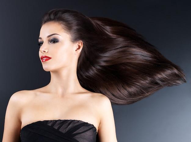 Jonge vrouw met lange bruine rechte haren op een donkere muur