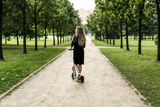 Jonge vrouw met lange haren op elektrische autoped. het meisje op de elektrische scooter.