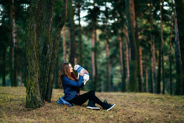 Jonge vrouw met lange zitting op grond voorbij bomen in bos met haar mooi chihuahuapuppy in handen.