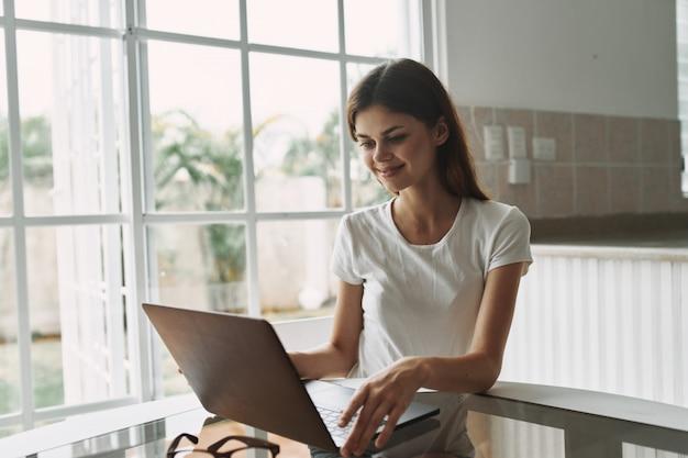 Jonge vrouw met laptop bij de en lijst die werkt rust
