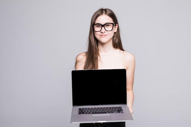 Jonge vrouw met laptop die de camera onder ogen zien die over witte muur wordt geïsoleerd