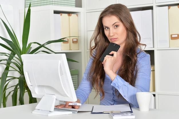 Jonge vrouw met laptop die op kantoor werkt