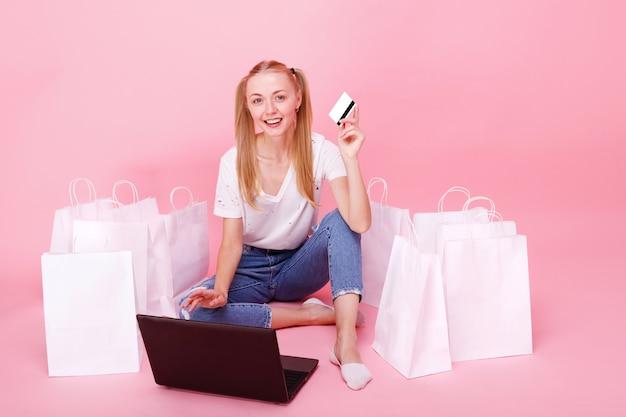 Jonge vrouw met laptop en papieren zakken met creditcard op roze