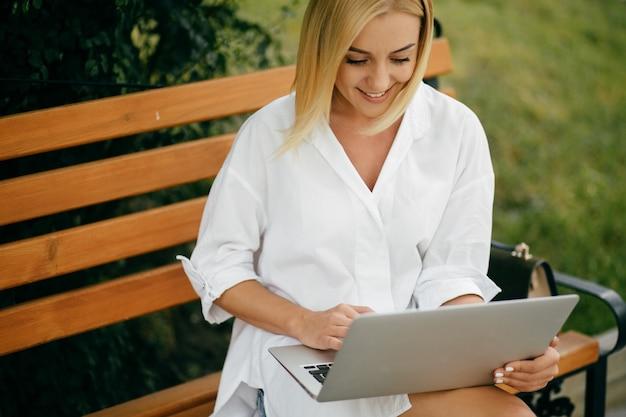 Jonge vrouw met laptop en slimme telefoon. mooi student meisje aan laptop buiten werken