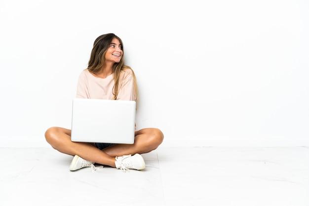 Jonge vrouw met laptop geïsoleerde zitting op de vloer