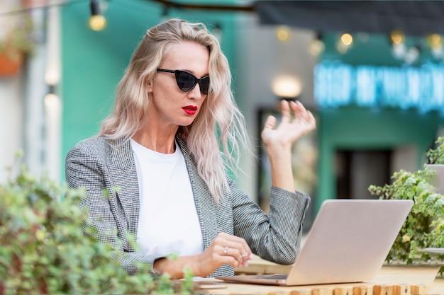 Jonge vrouw met laptop in een straatkoffie