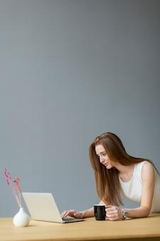 Jonge vrouw met laptop in het kantoor